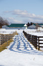 Farm fence and lines of shadows in winter time Stock Photo