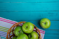 Farm fresh organic green apples in basket  on wooden retro blue Royalty Free Stock Photo
