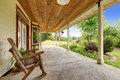 Farm house exterior entrance porch with rocking chair front yard landscape spacious Stock Photo