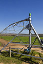 Farm irrigation equipment with blue skies and green fields Stock Photography