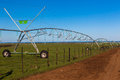 Farm mobile water irrigation sprinklers down the green field Royalty Free Stock Image
