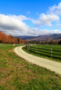 Farm road in the fall a dirt winding around livestock fences with foliage and mountains of vermont distance Stock Photo