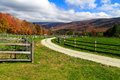 Farm road in the fall a dirt winding around livestock fences with foliage and mountains of vermont distance Stock Image