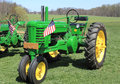 Farm tractor green parked in green farmland in spring with flags Stock Image