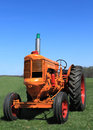 Farm tractor vintage orange parked in green farmland in spring on blue sky background Royalty Free Stock Photography