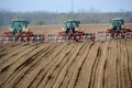 Farm tractors planting field Royalty Free Stock Photo