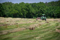 Farmer bales hay a his field using tractor Stock Photography