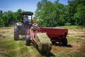 Farmer bales hay a his field using tractor Royalty Free Stock Image