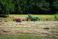 Farmer bales hay a his field using tractor Royalty Free Stock Images