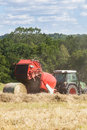 Farmer baling hay with a round baler dried grass for is open depositing bale behind line of raked cut grass ready Royalty Free Stock Images
