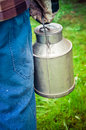 Farmer carrying a vintage dairy milk can cream in dirty blue work trousers plaid shirt and gloves goes forward background Royalty Free Stock Images
