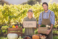 Farmer couple holding a basket and organic sign Royalty Free Stock Photo