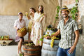 Farmer drinks wine while women pounding grapes in an old farm Royalty Free Stock Photography
