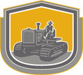Farmer driving tractor plowing farm shield retro illlustration of a worker riding a vintage field set inside crest done in style Stock Images