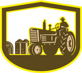 Farmer driving tractor plowing farm shield retro illlustration of a worker a vintage field set inside crest done in style on Stock Photos