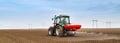 Farmer fertilizing arable land with nitrogen, phosphorus, potassium fertilizer. Royalty Free Stock Photo
