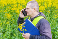 Farmer with folder and cell phone near yellow rape field