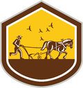 Farmer and horse plowing field shield retro illustration of famr viewed from side set inside shape done in woodcut style on Royalty Free Stock Photos