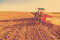 Farmer plowing stubble field with red tractor photo manipulated to achieve old cross processing xpro look Stock Images