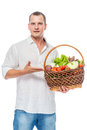Farmer presents organic vegetables in a basket on a white