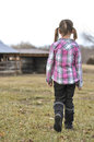 Farmer s daughter girl walking to the barn with her hair in pig tails wearing a pink plaid shirt and black boots Stock Images