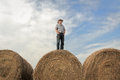 Farmer standing on a huge hay bale under a summer sky horizontal image of one wearing cowboy hat with his hands in his pockets Stock Image