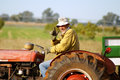 Farmer on tracktor happy waving from his old red clearly he is very happy being a Royalty Free Stock Photography