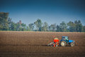 Farmer with tractor seeding crops in the field at Royalty Free Stock Photo