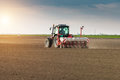 Farmer with tractor seeding - sowing crops at agricultural field Royalty Free Stock Photo