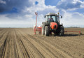 Farmer in tractor sowing crops at field with seed scattering agricultural machine Royalty Free Stock Photography