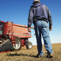 Farmer walking toward combine. Royalty Free Stock Images