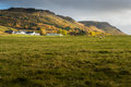 Farmhouse with green field surround mountain range background in autumn season Stock Photos