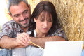 Farming couple sat with laptop computer Stock Image