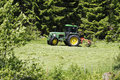 Farming tractor in action large mowing green fields Stock Photo