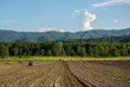 Farming with tractor and plow in field with mountain Papuk in th