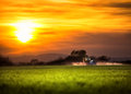 Farming tractor plowing and spraying at sunset