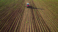 Farming tractor plowing and spraying on wheat field