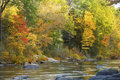 Farmington River flows by vibrant fall foliage in Canton, Connec