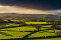 Farmland and coutryside with stormy clouds rolling pouring rain at sunset view from hill top long shadows Stock Photo