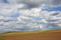 Farmland field with cloudy sky Stock Photo