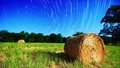 Farmland and stars moonlit hay bale under star trails on a farm in north georgia usa Stock Photography