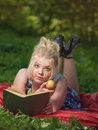 The fascinating book girl lays on a glade reads and eats an apple Royalty Free Stock Image