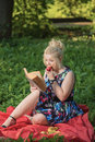 The fascinating book girl sits on a glade and reads Royalty Free Stock Photo