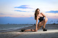 Fascinating curly brunette young showing her perfect body on the beach at sunset Stock Photos