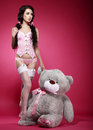 Fascinating young woman in pink lingerie with her fondling soft toy sexy female teddy bear Royalty Free Stock Photo