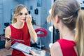 Fashio Portrait of beautiful young girl making make-up near mirror