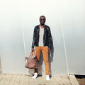 Fashion african man model wearing sunglasses and black leather jacket with bag Royalty Free Stock Photo