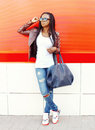 Fashion african woman with bag in city over red Royalty Free Stock Photo
