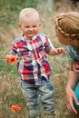 Fashion baby boy and his mother smelling flower wearing checkered shirt Stock Photography