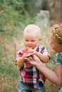 Fashion baby boy and his mother smelling flower wearing checkered shirt Stock Image